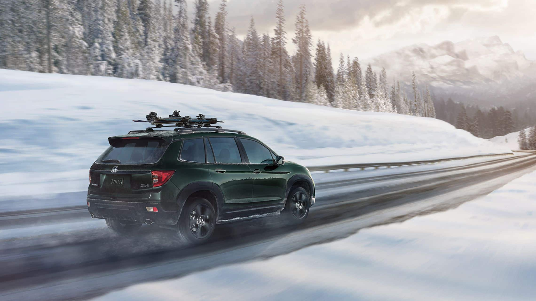 Passenger-side rear 3/4 view of 2019 Honda Passport AWD Elite in Black Forest Pearl with accessory ski/snowboard attachment driving on a snowy mountain  road.