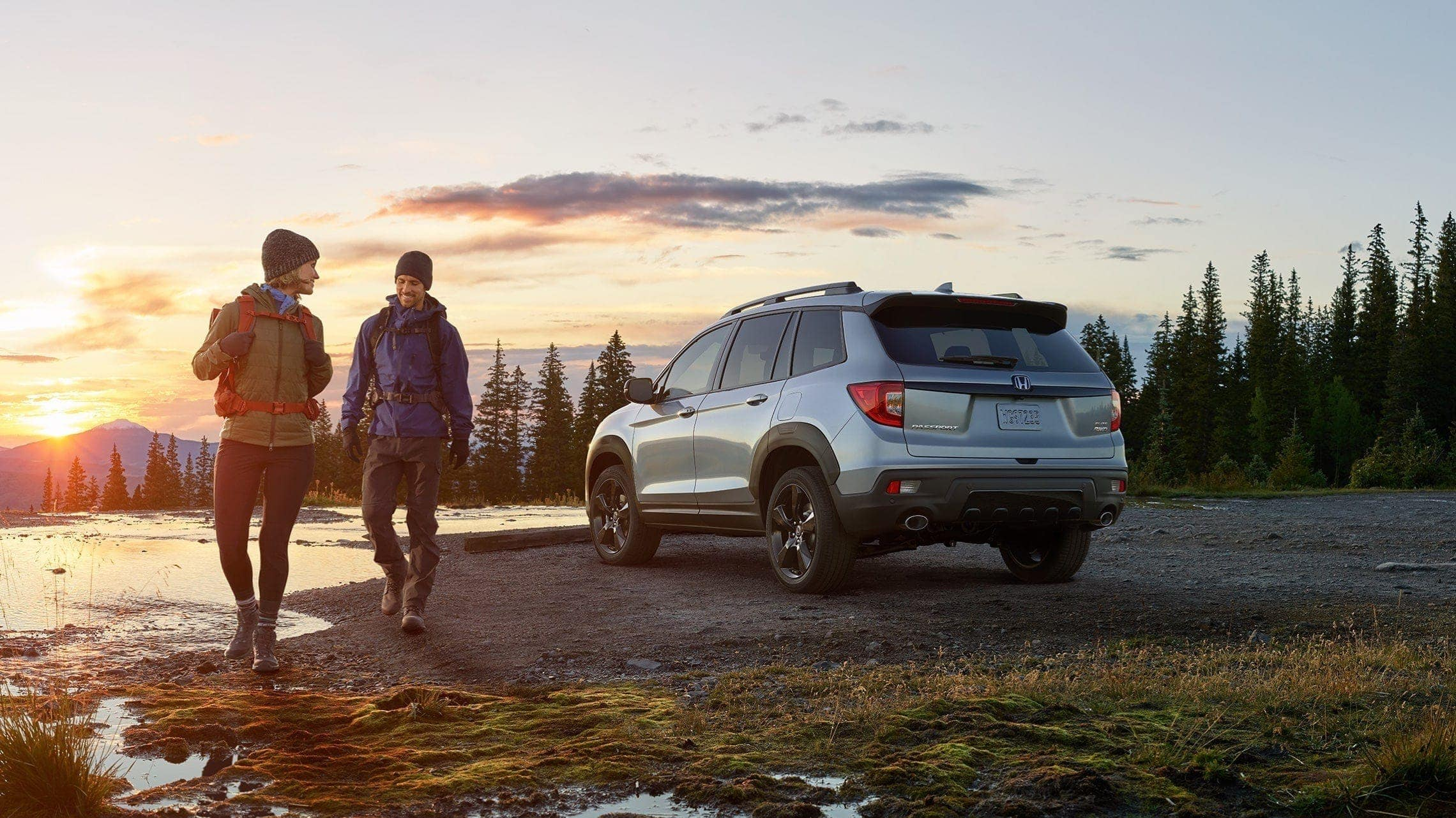 Driver-side 3/4 rear of 2019 Honda Passport Elite in Lunar Silver Metallic with accessory fender flares, at pond location with male and female hikers in foreground.