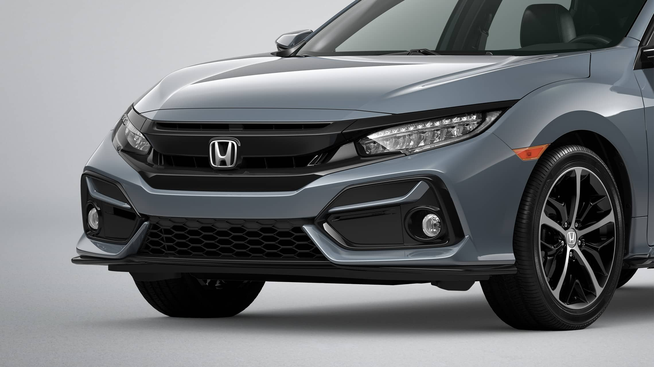 Front 3/4 driver-side close-up view of the 2020 Honda Civic Sport Touring Hatchback in Sonic Gray Pearl.